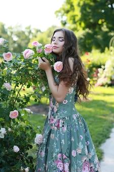 Giovane bella ragazza vicino a un cespuglio con rose nel parco