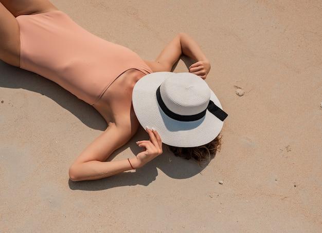 Giovane bella ragazza in bikini di lusso nudo in posa sulla spiaggia di sabbia bianca blue ocean surface
