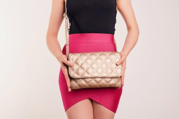Giovane bella ragazza in gonna rosa che tiene borsa a mano marrone. borsa alla moda nelle mani della donna.