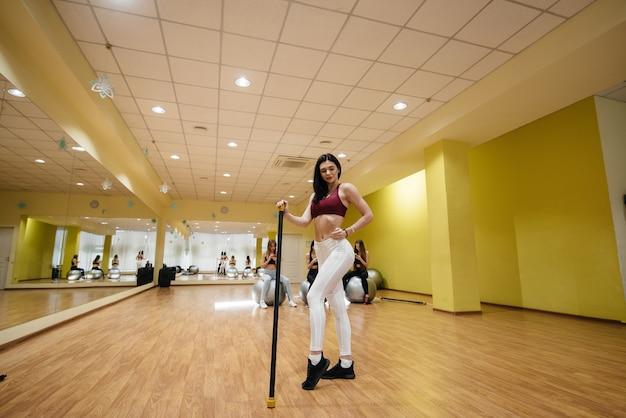 Giovane bella ragazza che posa dopo le sessioni di gruppo in palestra. uno stile di vita sano.