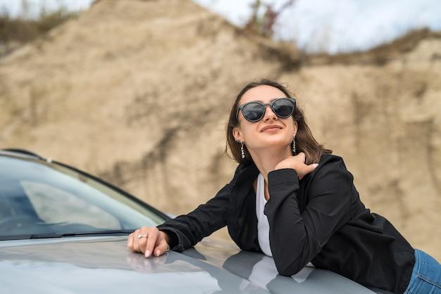Giovane bella ragazza che posa in un'auto sulla natura che viaggia per le vacanze estive del paese