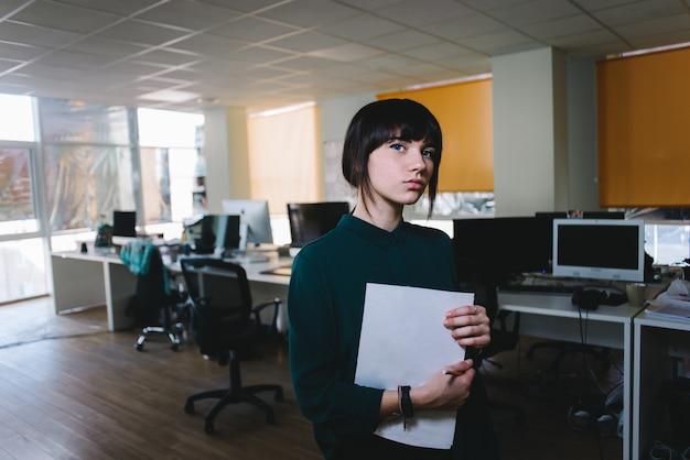 Giovane bella ragazza che posa con le carte sui precedenti dello spazio ufficio. concetto di affari. ufficio moderno