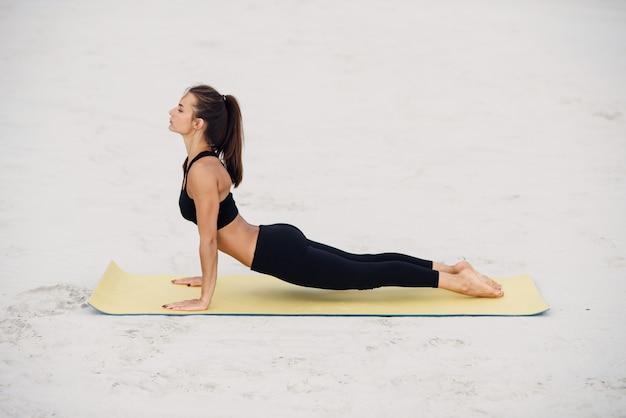 Posa di pratica della cobra di yoga della giovane bella ragazza sulla spiaggia al tramonto. yoga sport fitness e concetto di stile di vita sano.