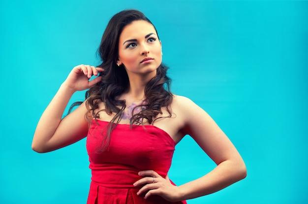 Giovane bella ragazza in abito rosso, con il trucco, raddrizza i capelli con la mano. isolato su una parete blu