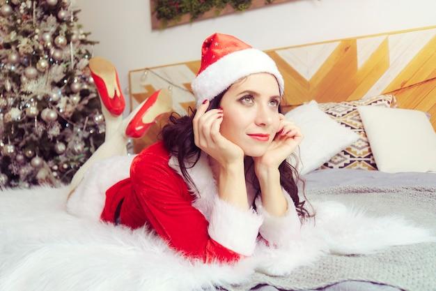 La giovane bella ragazza in un vestito rosso di babbo natale è sdraiata sul letto e guarda sognante in lontananza sullo sfondo dell'appartamento decorato per natale.