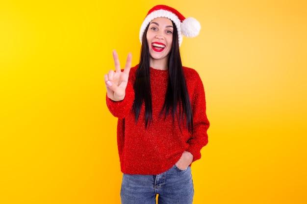 Giovane bella ragazza in un cappello rosso della santa. donna felice e sorridente che mostra due dita.