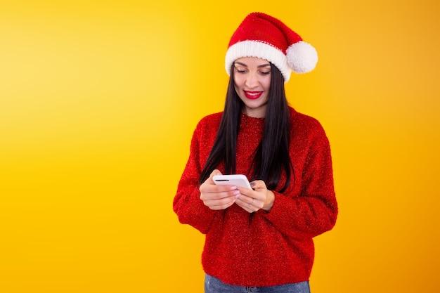 La giovane bella ragazza in un cappello rosso della santa tiene un telefono nelle sue mani contenuto di sconto di natale