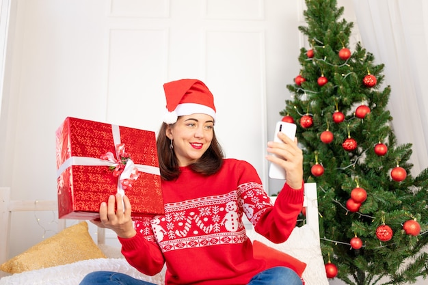 Una giovane bella ragazza con un maglione rosso e un cappello sta effettuando una videochiamata con un regalo