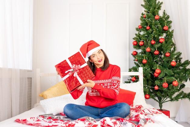 Una giovane bella ragazza con un maglione rosso e un cappello è seduta a casa sul letto vicino all'albero di natale con un grande regalo rosso