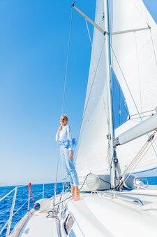 Giovane bella ragazza che si distende su yacht in grecia