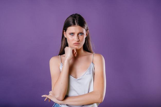 Una giovane bella ragazza mostra emozioni e sorrisi su un muro viola. ragazze per la pubblicità.