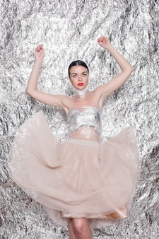 Giovane bella ragazza su uno sfondo d'argento. donna artistica in stile con trucco di fantasia di arte. creatività. ritratto di moda di una giovane bella ragazza elegante con festa brillante
