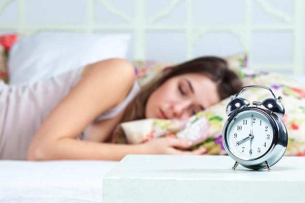 La giovane bella ragazza che dorme nel letto. il servizio orologio è in primo piano
