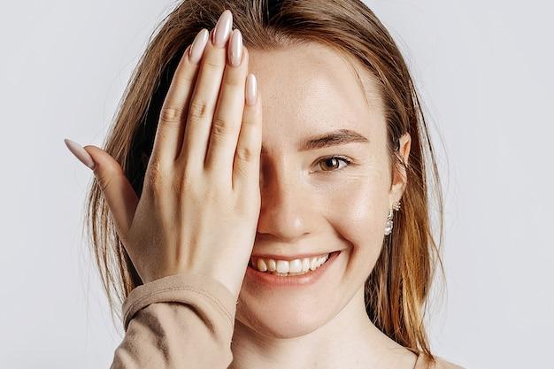 Giovane bella ragazza sorride e copre metà del viso con la mano su uno spazio bianco isolato