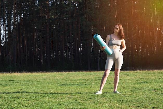 Una giovane bella ragazza in uniforme sportiva e un tappetino da yoga tra le mani è venuta a fare sport. allenamento all'aria aperta, al parco, d'estate, al sole. yoga nel concetto di parco.