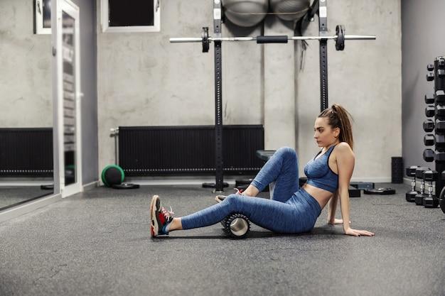 Una giovane bella ragazza in abiti sportivi massaggia i muscoli delle gambe con un massaggio con rulli sportivi roller