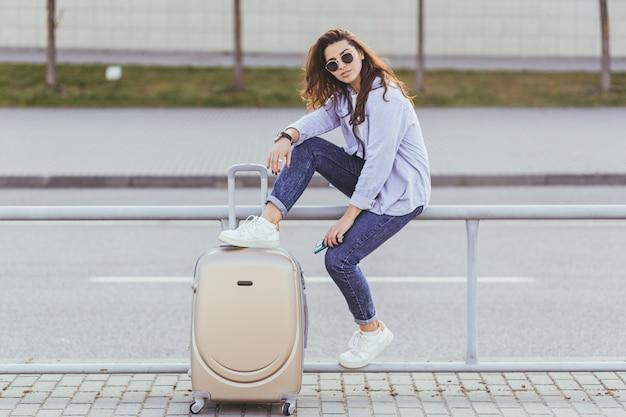 Una giovane e bella studentessa lascia l'aeroporto in una nuova città e aspetta un taxi