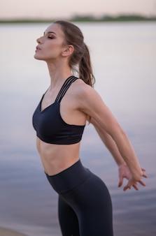 Giovane bella ragazza in fase di riscaldamento prima di fare yoga in riva al mare al tramonto