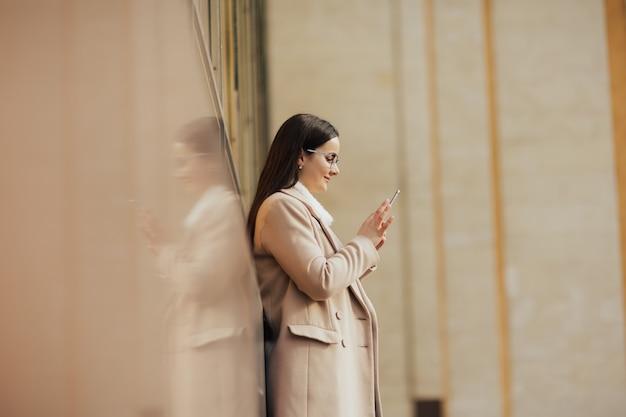 Giovane bella ragazza che indossa un elegante cappotto beige e occhiali da vista scrive sms su smartphone vicino all'edificio.