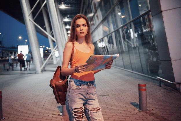 Una giovane bella ragazza con uno zaino dietro le spalle in piedi sulla strada vicino a un aeroporto. è appena arrivata dal resto ed è molto felice!
