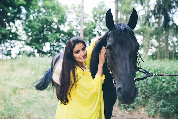 Giovane bella ragazza con i capelli neri che si siede su un cavallo