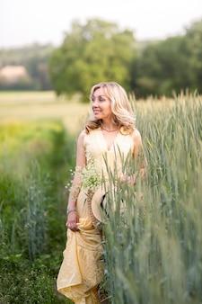 Giovane bella ragazza con borsa intrecciata, cappello di paglia e bouquet di colore nel campo