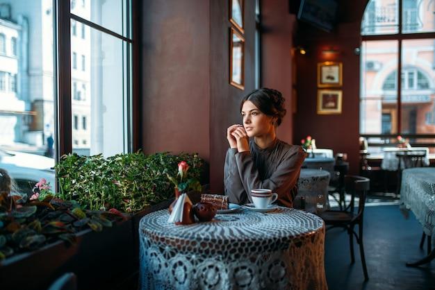 Una giovane bella ragazza con una tazza di caffè e dessert in un caffè in stile retrò.