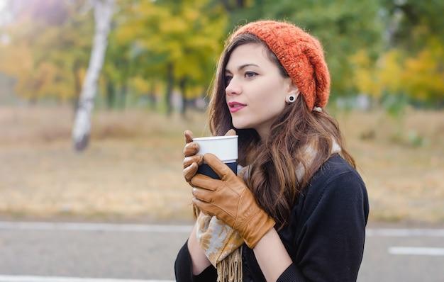Giovane bella ragazza con una tazza di caffè (tè) nel tappo nel parco in autunno. autunno caldo clima soleggiato.
