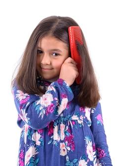 Giovane bella ragazza con il pettine dei capelli