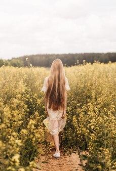 Una giovane bella ragazza con i capelli lunghi cammina in un campo di colza, guarda in lontananza. retrovisore. verticale