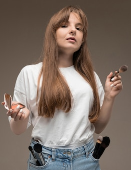 Una giovane bella ragazza con lunghi capelli ondulati rustici, trucco nudo, indossa una maglia bianca, tiene un pennello per il trucco e arrossisce