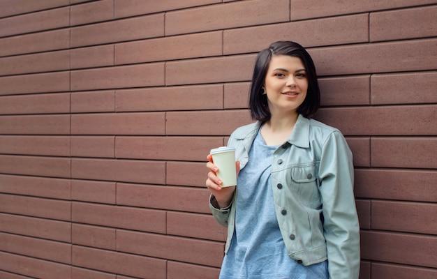 Giovane bella ragazza con piercing nelle orecchie, in una giacca bianca e con una tazza di caffè in mano è in piedi vicino al muro di mattoni.