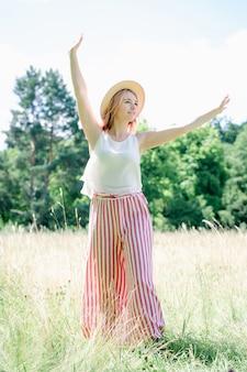 Giovane bella ragazza con i capelli rosa nel cappello estivo sulla radura
