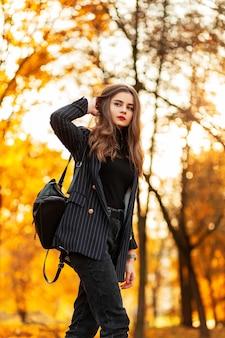 Giovane bella ragazza con labbra rosse in abiti alla moda con blazer, maglione e zaino cammina in un parco autunnale con fogliame giallo al tramonto