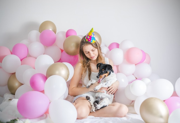 La giovane bella ragazza si è svegliata circondata da palloncini il giorno di compleanno con il suo cane