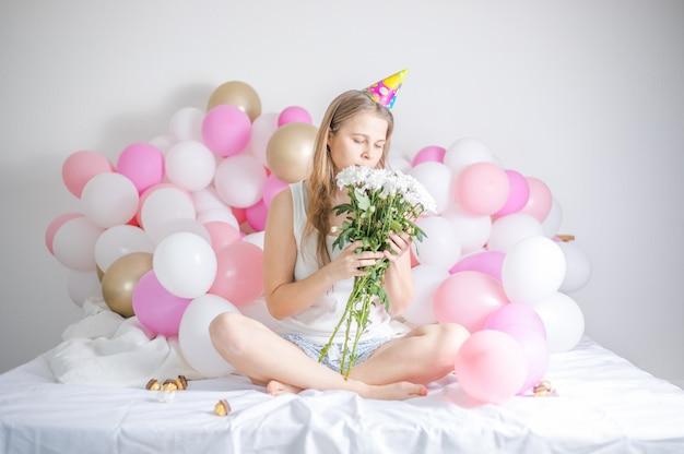 Giovane bella ragazza si è svegliata circondata da palloncini il giorno del compleanno