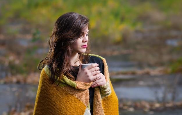 Giovane bella ragazza avvolta in una coperta e una tazza di caffè (tè) nelle mani della vita all'aria aperta in serata autunnale.