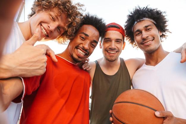 Giovani bei ragazzi sorridenti e prendendo selfie, mentre giocano a basket al parco giochi all'aperto durante la giornata di sole estivo