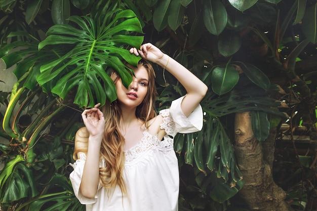 Modello di giovane bella ragazza bionda felice su sfondo di piante tropicali con foglia verde