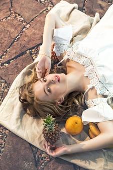 Giovane bella modella bionda felice che si trova su un copriletto di lino con frutta
