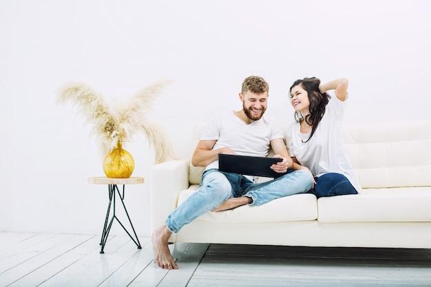 Giovane bella e felice coppia uomo e donna a casa con tablet in interni bianchi