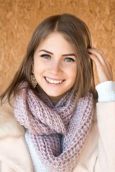 Giovane bella ragazza sorridente positiva felice con il ritratto tricottato della sciarpa