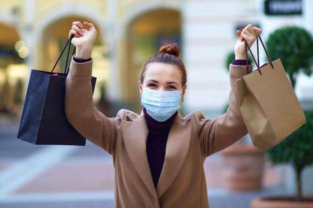 Giovane bella donna elegante felice sta facendo shopping nel centro commerciale, indossando la mascherina medica protettiva su di lei