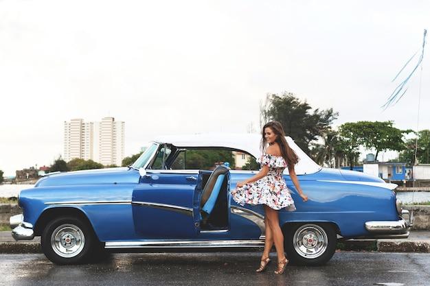 Giovane, bella e felice donna alla guida di un'auto decappottabile retrò