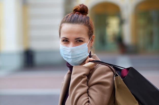 Giovane bella donna felice sta facendo shopping nel centro commerciale, indossando la mascherina medica protettiva sul viso