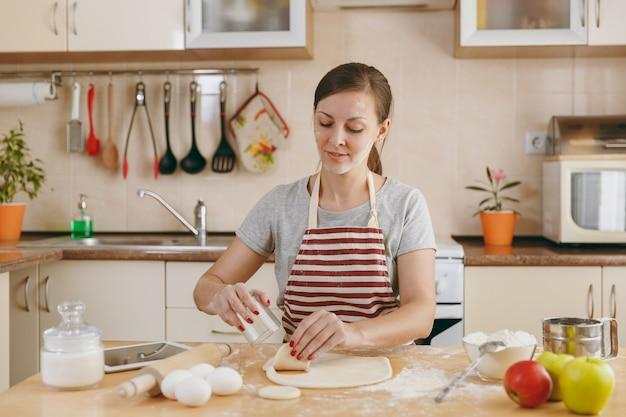 La giovane bella donna felice seduta a un tavolo con la farina e ritaglia un bicchiere in un cerchio di pasta per gnocchi in cucina. cucinare a casa. prepara da mangiare.