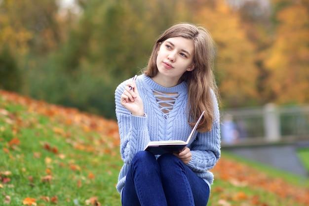Giovane bella donna felice, studente adolescente sta studiando all'aperto nel parco scrivendo in taccuino o