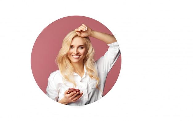 Giovane bella donna felice che per mezzo di uno smartphone. sbircia da un buco rotondo nel muro. muro bianco. spazio vuoto per il testo.