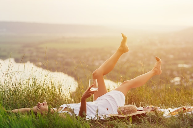 Giovane bella donna felice con vino bianco in mano è sdraiata sulla coperta e si gode il momento perfetto al picnic estivo.