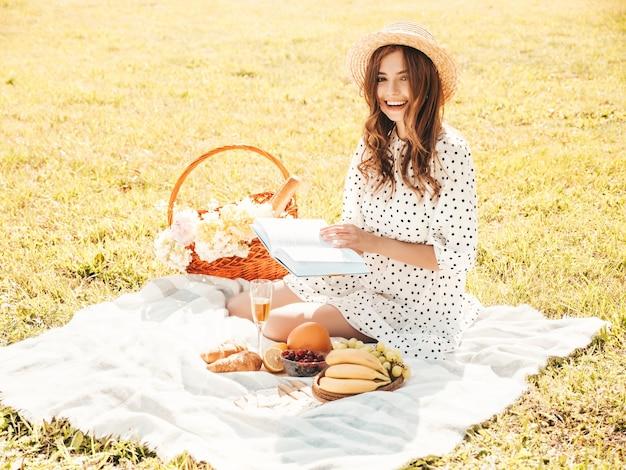 Giovane bella donna hipster in jeans estivi alla moda, maglietta rosa e cappello. donna spensierata che fa picnic all'esterno.